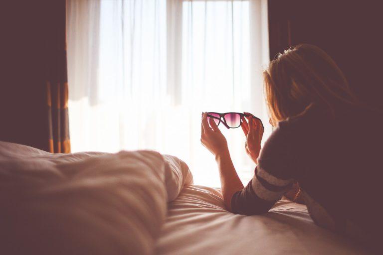 Mujer mirando la ventana a través de las gafas